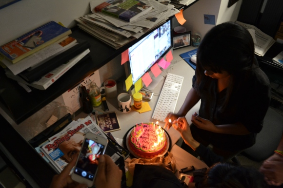 Editors from my college newspaper prepare a cake for a fellow editor after a long day of work.