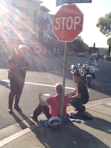 A Daily Titan reporter, right, talks to a man who was hit by a car while riding his motorcycle.