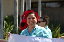 Brenda Ramirez, a children's librarian, holds a sign for a storytime program