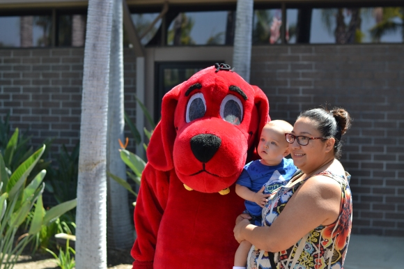 A family takes a picture with Clifford in front of the library