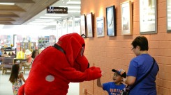 A boy high-fives Clifford inside the Placentia Library