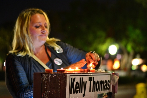 A woman lights candles atop the Kelly Thomas memorial at the Fullerton Transportation Center.