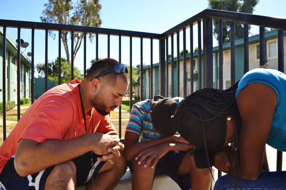 Adrian, left, prays with two teens in Watts, Calif., at a youth ministry outreach, in Sept. 2013.