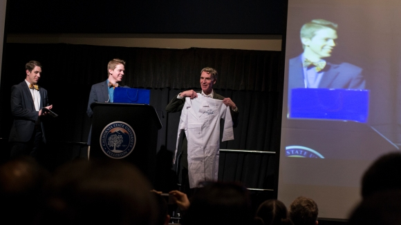 Student leaders give Bill Nye a CSUF lab coat following his keynote.