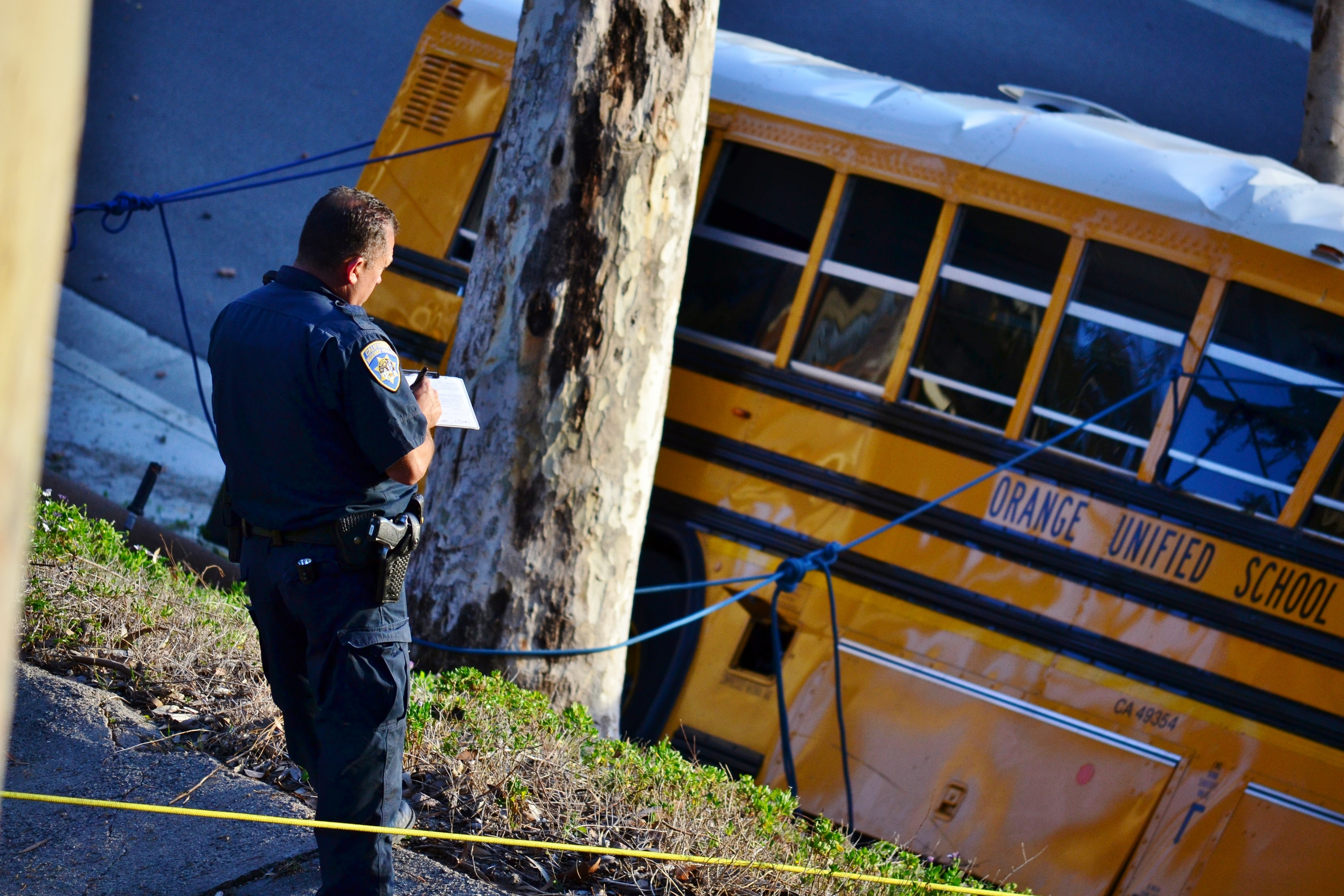 A California Highway Patrol officer takes notes of the school bus crash on late Thursday afternoon April 24, 2014.