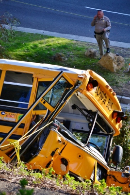 A California Highway Patrol officer talks on the phone near the crashed bus on Thursday afternoon.