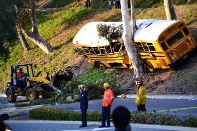 Workers break up a tree that fell as the result of a school bus crashing into a tree in Anaheim Hills in April 2014, resulting in about a dozen injuries.