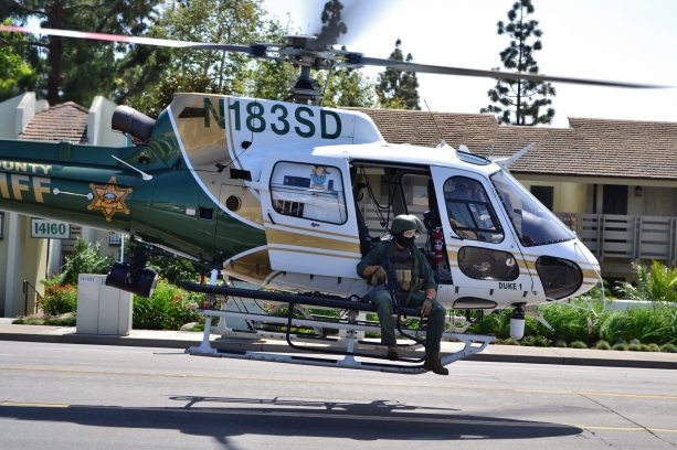 An Orange County Sheriff's helicopter with armed SWAT officers on both ledges takes off to search for an allegedly armed suspect in Tustin.