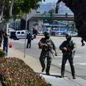 In this heavily cropped image, SWAT officers walk on Red Hill Avenue en route to a helicopter