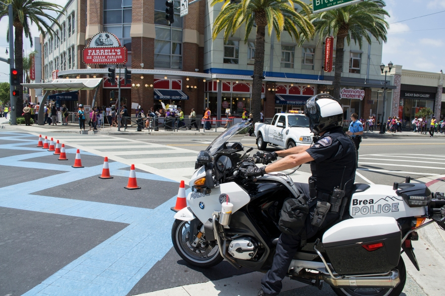 A Brea police motorocycle officer watches as immigration reform protesters march through downtown Brea on June 27, 2014.