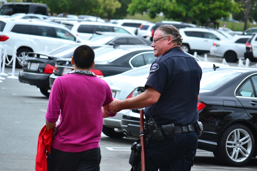 A Brea police officer escorts a man off the premesis of the mall's parking lot on Friday, Sept. 18.