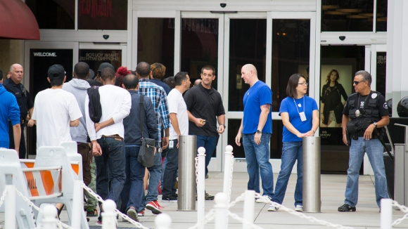 A Brea police officer, far right, chats with an Apple Store employee as a wave of about 20 customers, left, is allowed to enter the mall around 10 a.m. on Friday, Sept. 18.
