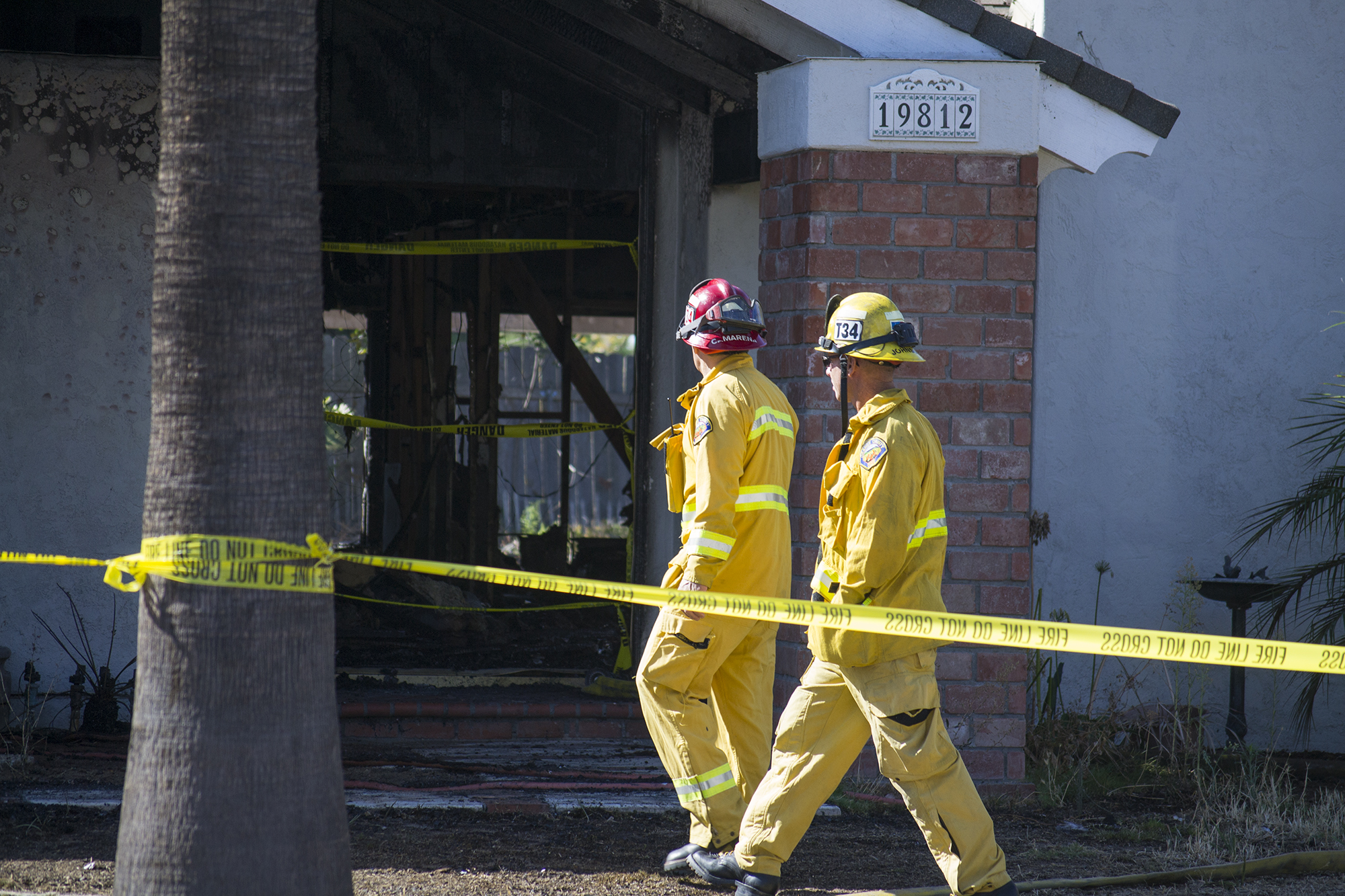 Firefighters investigate the burned house on Thursday morning, Sept. 18.