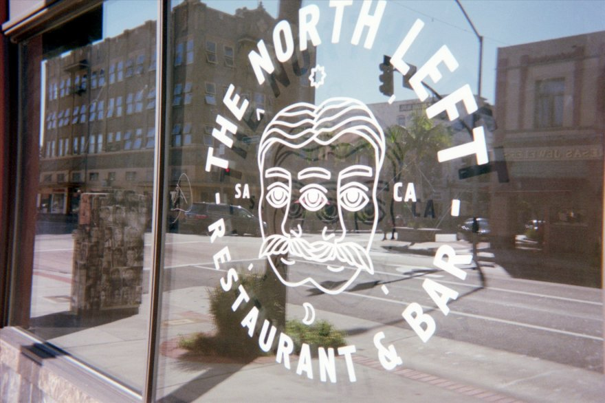 Views of downtown Santa Ana are seen in a reflection in a window for the North Left bar, photographed in September 2014. Digital scan from a Fujifilm 400 disposable camera processed in January 2015.